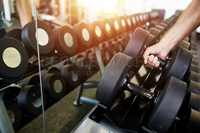 Buy stock photo Cropped shot of a man's hand lifting a dumbbell off a rack in a gym