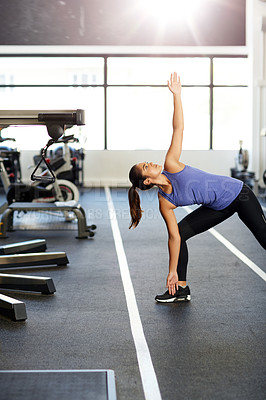 Buy stock photo Shot of a young woman warming up in the gym