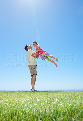 Buy stock photo Full length of man standing on grass and picking up his daughter - copyspace