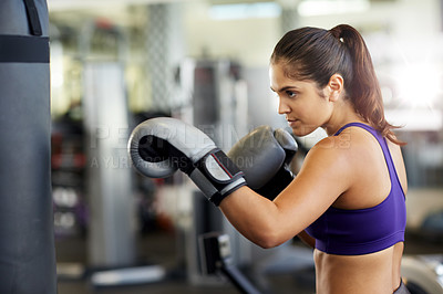 Buy stock photo Cropped shot of a young woman working on the punching bag in the gym