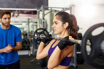 Buy stock photo Cropped shot of a young woman lifting a barbell in the gym with her personal trainer