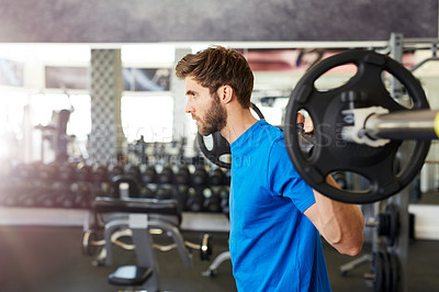 Buy stock photo Cropped shot of a young man lifting a barbell in the gym