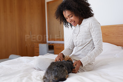 Buy stock photo Shot of a young woman playing with her dog in her bed