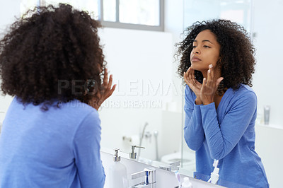 Buy stock photo Shot of a young woman looking at herself in the bathroom mirror