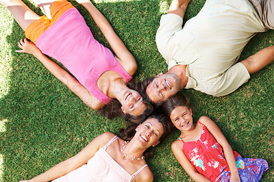 Buy stock photo Top view of an attractive family lying on grass with heads together and smiling