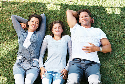 Buy stock photo Top view of family relaxing on grass and giving you an attractive smile