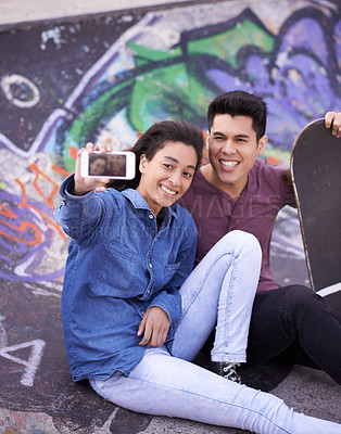 Buy stock photo Shot of a young couple taking a selfie together at a skatepark