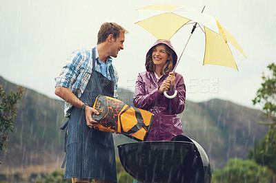 Buy stock photo Shot of a couple happily  barbecuing in the rain