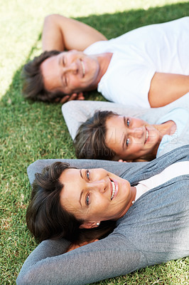 Buy stock photo Closeup portrait of woman relaxing on grass with daughter and husband in background