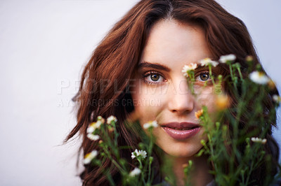 Buy stock photo Portrait of a young woman holding a bunch of wild flowers