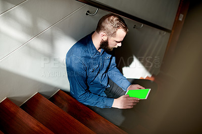 Buy stock photo High angle shot of a young man using his digital tablet while sitting on a staircase at home
