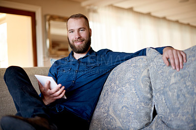 Buy stock photo Cropped portrait of a young man using his digital tablet while sitting on a sofa at home