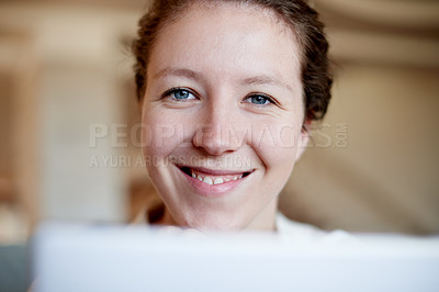 Buy stock photo Cropped portrait of a young woman using her laptop at home