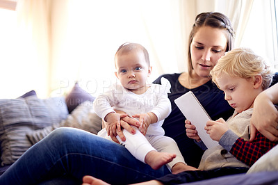 Buy stock photo Shot of a young family sitting with a digital tablet at home