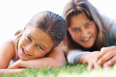 Buy stock photo Closeup of young smiling girl relaxing on grass with her sister
