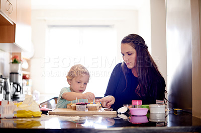 Buy stock photo Shot of a little boy helping his mom to decorate cupcakes in the kitchen