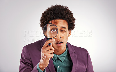 Buy stock photo Studio shot of a young man using a magnifying glass against a gray background