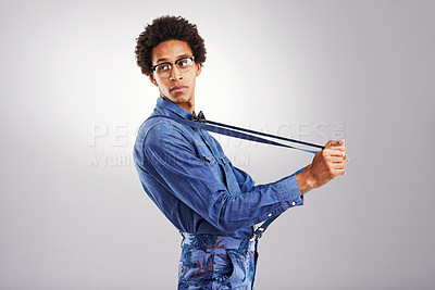 Buy stock photo Studio shot of a stylishly dressed young man pulling on his suspenders