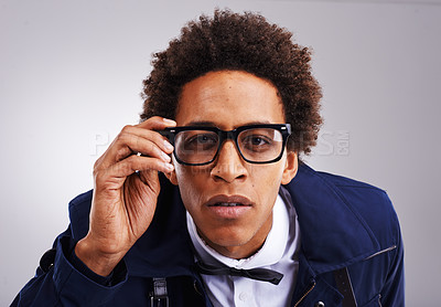 Buy stock photo Closeup shot of a young man wearing glasses against a gray background
