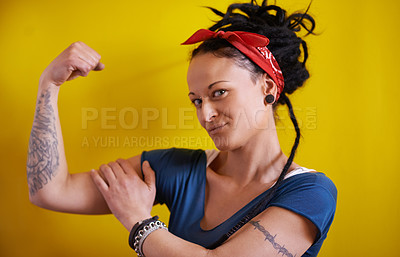 Buy stock photo Shot of a woman with dreadlocks flexing her muscles and showing off her tattoo