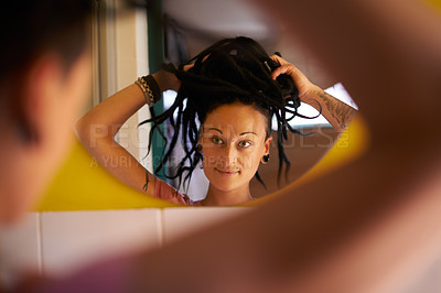 Buy stock photo Cropped shot of a young woman with dreadlocks fixing her hair in the mirror