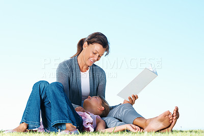 Buy stock photo Smiling woman sitting on grass and reading book with daughter lying on her lap - copyspace
