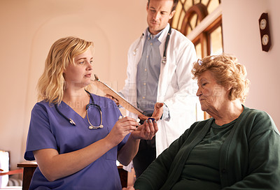 Buy stock photo Shot of a doctor and nurse giving a senior woman her medicine at a retirement home
