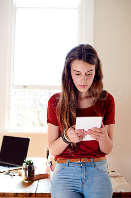 Buy stock photo Shot of a teenage girl using her digital tablet at home