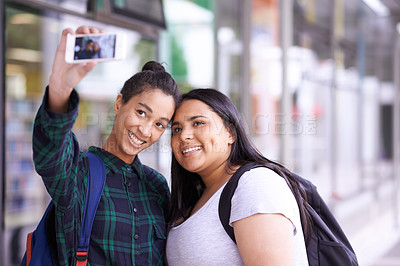 Buy stock photo Shot of two smiling university students taking a selfie on campus