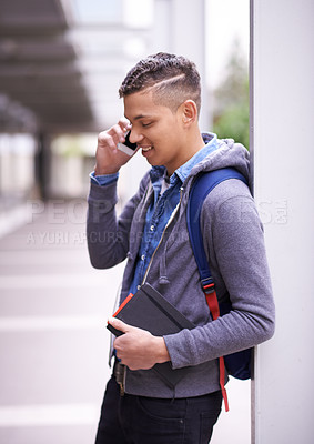 Buy stock photo Shot of a university student talking on his phone while standing on campus