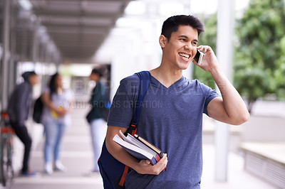 Buy stock photo Shot of a university student using his cellphone on campus