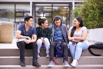 Buy stock photo Shot of a group of university students sitting on some steps on campus