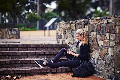 Buy stock photo Shot of a sporty young woman listening to music while sitting outside