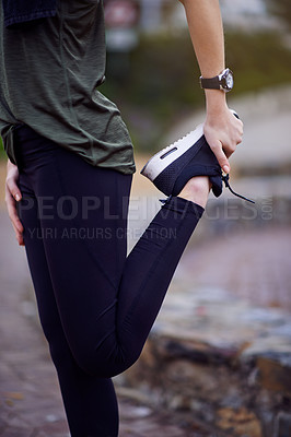 Buy stock photo Cropped shot of a young woman stretching her legs before a run