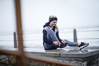 Buy stock photo Shot of a young woman tying her shoelaces before a run