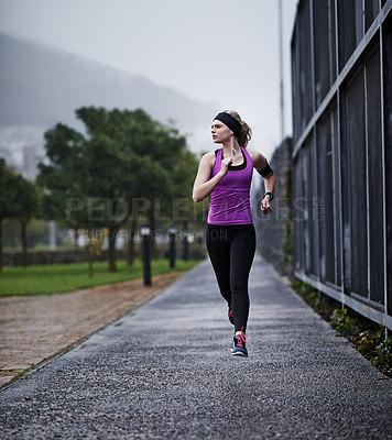 Buy stock photo Shot of a young woman running along a path