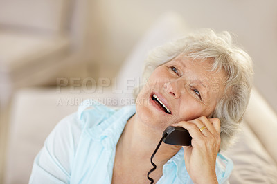 Buy stock photo A senior woman talking on the phone while looking upwards