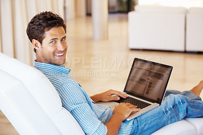 Buy stock photo Smiling man sitting in his armchair at home and surfing internet on his laptop