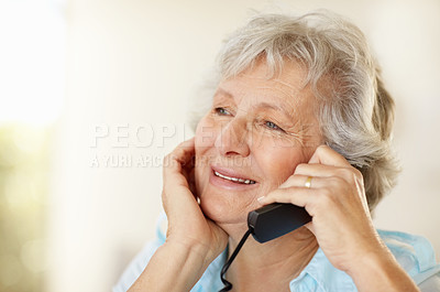 Buy stock photo A senior woman talking on the telephone and looking a little sad