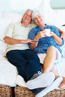 Buy stock photo Portrait of senior couple sitting together on a sofa and enjoying the moment