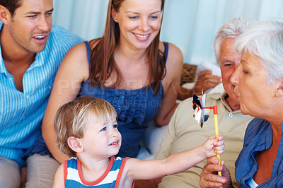 Buy stock photo Cute kid holding hand windmill with grandmother setting it into motion by blowing air