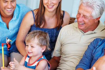 Buy stock photo Young boy sitting on a sofa with family and playing with a paper windmill