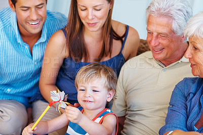 Buy stock photo Little boy sitting on a sofa with family and playing with a paper windmill