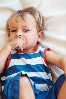 Buy stock photo Closeup portrait of little kid lying on sofa with thumb in mouth
