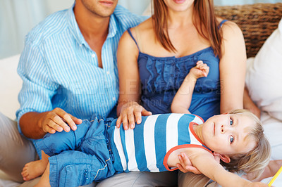 Buy stock photo Mother and father sitting on sofa and holding their son