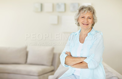 Buy stock photo Portrait of a senior woman sitting on the sofa with her arms folded