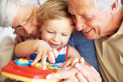 Buy stock photo Closeup of little boy playing a toy with his grandparents