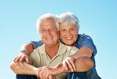 Buy stock photo Portrait of senior couple giving you an attractive smile against sky with woman embracing man from behind