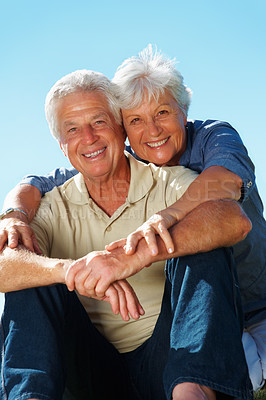 Buy stock photo Portrait of senior couple sitting outside with woman embracing man from behind