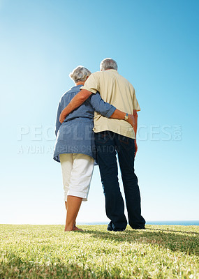 Buy stock photo Rear view of senior couple standing together on grass with arms around